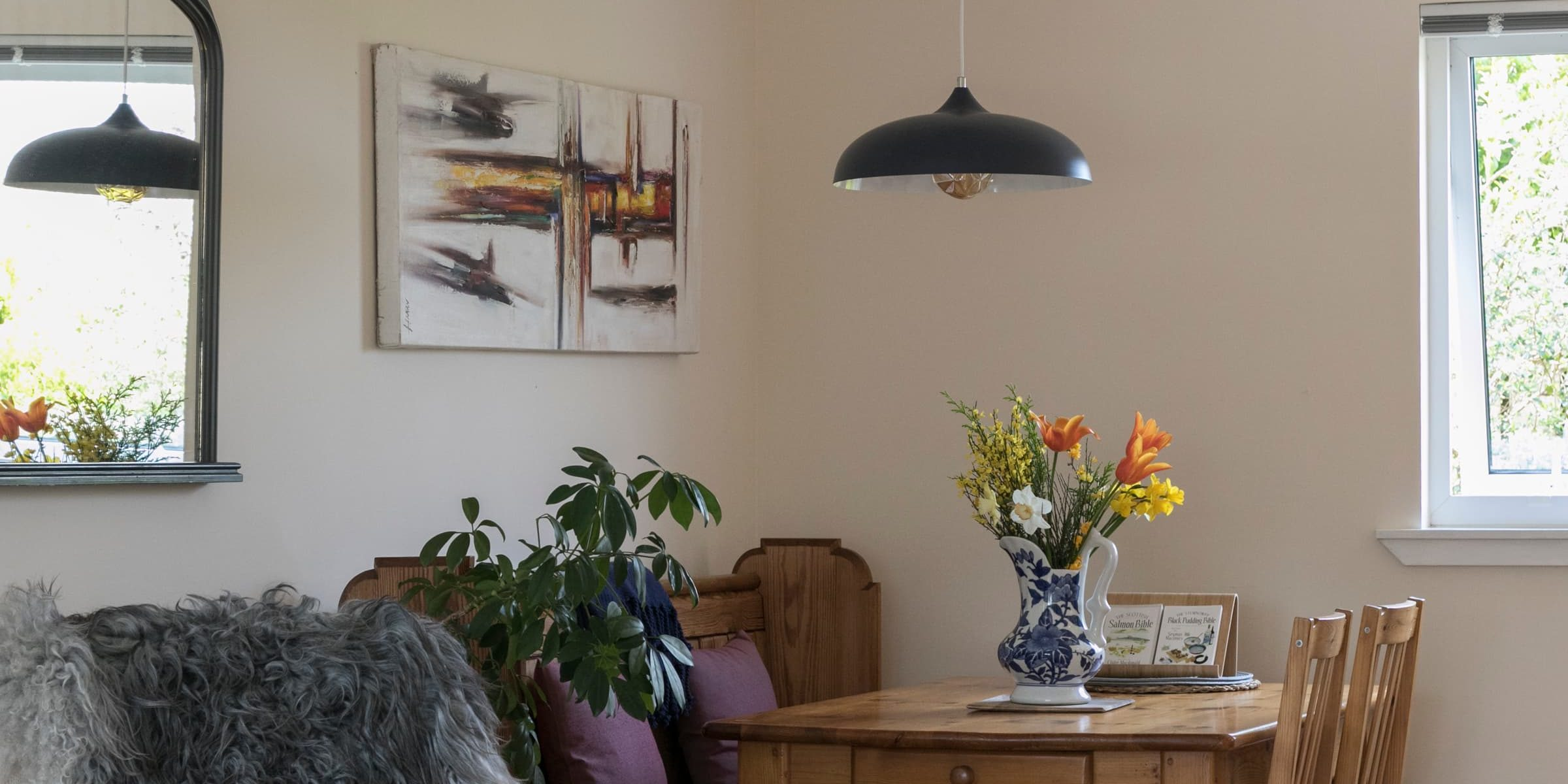living room and dining area with sheep rug and flowers