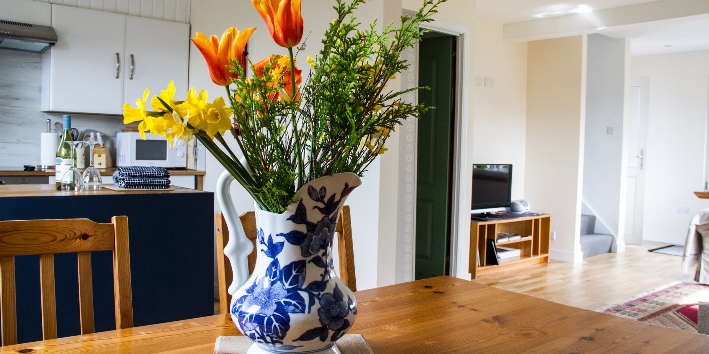 diningr room table with orange flower vase and colourful flowers